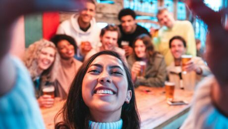 young woman taking selfie of herself with group