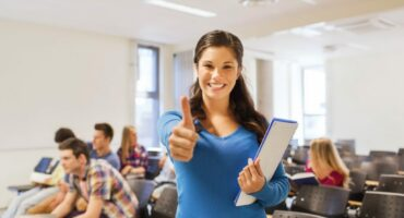 woman in lecture hall putting her thumb up