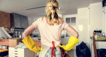 young woman with gloves about to clean an apartment